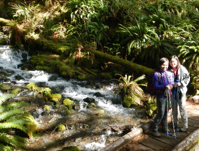 Two hikers stand smiling on a small bridge over an Olympic Peninsula creek with huge sword ferns growing along the bank