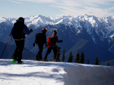 Three people on snowshoes are treated to an amazing view of snow-clad Olympic Mountains at Hurricane Ridge