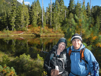 A couple stands next to a reflection lake with beautiful fall color