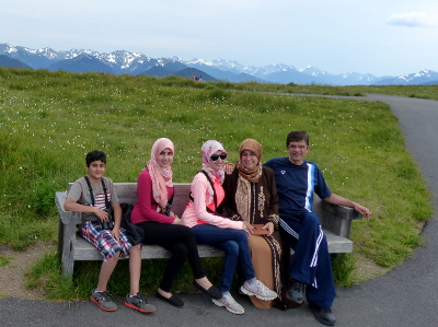 Parents and their three children sit on a wooden bench at Hurricane Ridge with the snowy Olympic Mountains in the distance