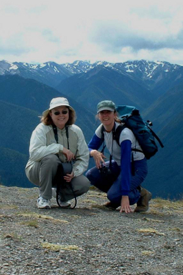 Two Olympic National Park hikers smiling with the snowy Olympic Mountains in the background