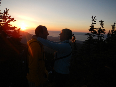Two embracing hikers look into the eyes of their significant other as the sun sets in the background