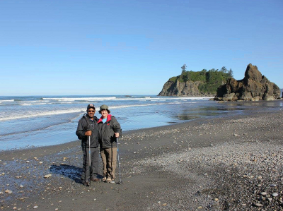 Two participants posing at Ruby Beach in Olympic National Park with waves crashing in the background