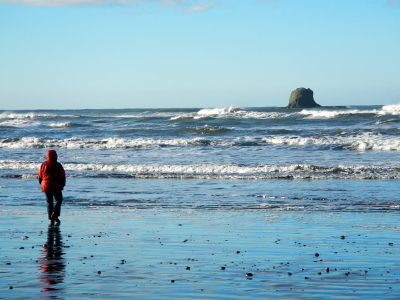 A woman in a red coat looks out towards a seastack at Ruby Beach in Olympic National Park