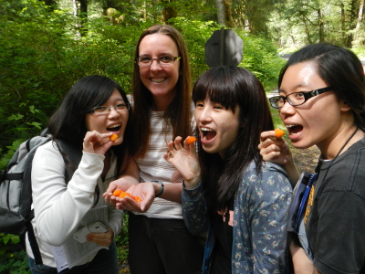 Three smiling participants hold yellow salmonberries up to their mouth while their smiling Experience Olympic guide cups more of the delicious berries in her hands
