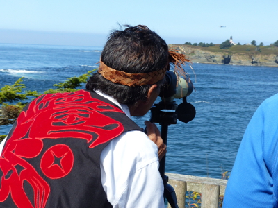 A Cape Flattery naturalist dressed in vivid read and black looks through a spotting scope at Tatoosh Island in the distance