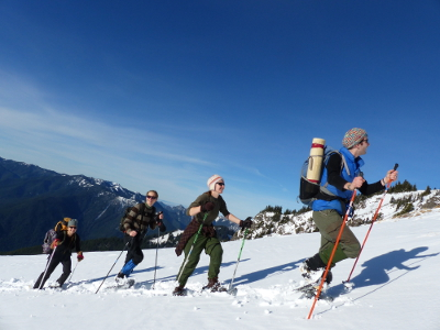 Four smiling participants are enjoying a sunny winter day on snowshoes during a Hurricane Ridge snowshoe tour