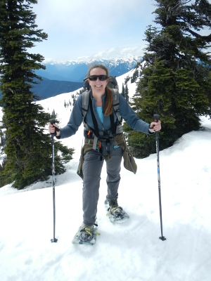 Your Olympic Guide is holding ski poles and smiling as she stands on many feet of snow in her snowshoes with the snowclad Olympic mountains in the background