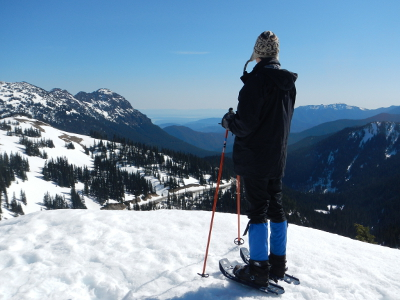 An Olympic National Park hiker stands on snowshoes looking towards the Strait of Juan de Fuca at Hurricane Ridge in winter