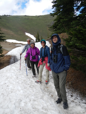 Hurricane Hill is pictured in the background as four participants stopping to pose while hiking on a snow-covered Olympic National Park trail at Hurricane Ridge