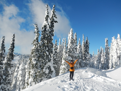 Olympic National Park visitor raises her hands in joy with snow covered subalpine fir trees in the background
