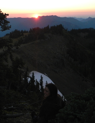 A smiling hiker sits enjoying the sunset over the Strait of Juan de Fuca and some of the Olympic foothills