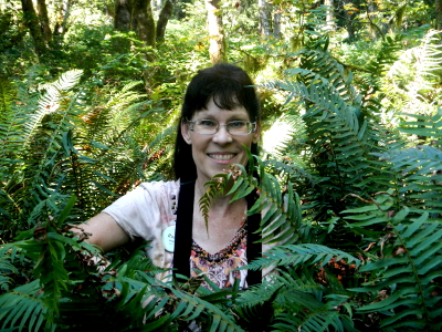 Renee smiling and peering through sword ferns as tall as she is