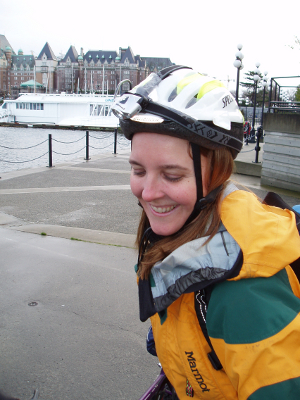 A girl on her bike wearing a helmet smiles with the Empress Hotel in Victoria, Canada in the background