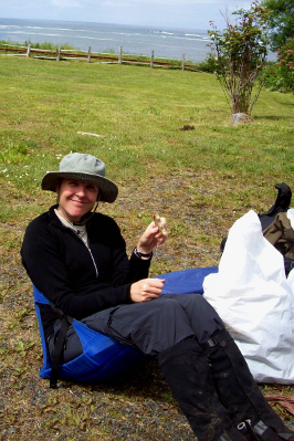 Hiker seated in a packable chair with a nylon hat, wood shirt, nylon hiking pants, and gaiters