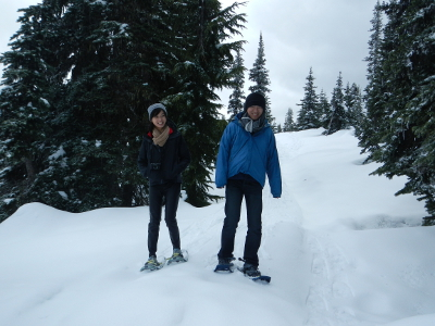 Two smiling hikers tentatively walk on snowshoes through a stand of subalpine fir in the Olympic mountains