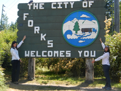 Two teenage girls wearing the same outfit and standing in the same manner on either side of the now famous Welcome to Forks sign from Twilight