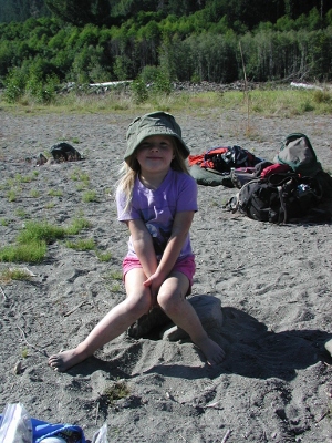 Young girl with a sun hat seated on a rock in an Elwha River sandbar