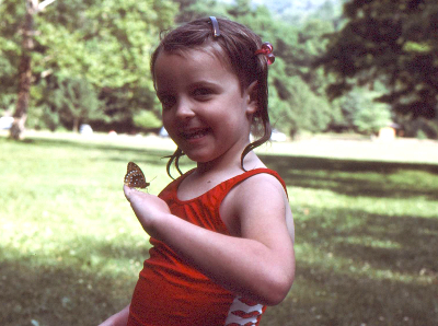 A five year old girl in a red bathing suit has a butterfly resting on her hand