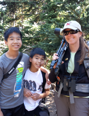 Olympic Guide Carolyn Wilcox stands smiling with her backpack and spotting scope over one shoulder with two young tour participants